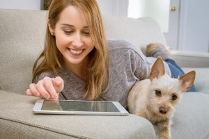 Woman on couch with puppy using ipad